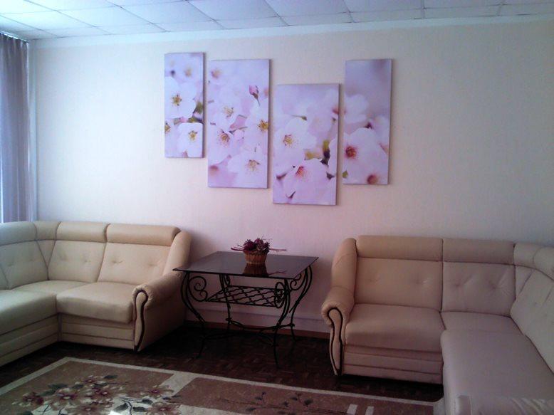 Светлая картина над диванами и столом