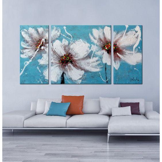 Картина белые цветы на синем фоне над диваном